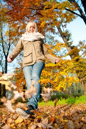 young woman playing with autumn leaves photo