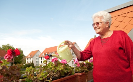 old woman watering flowers on the balcony