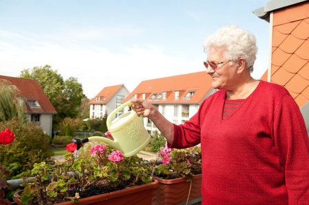 old woman watering flowers on the balcony photo