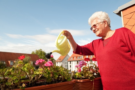 old woman watering flowers on the balcony Stock Photo - 12055891