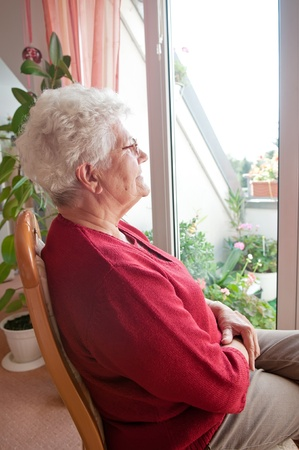 sadness: lonely old woman looks out the window Stock Photo