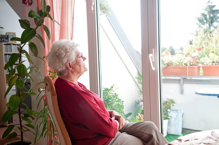 lonely old woman looks out the window Stock Photo
