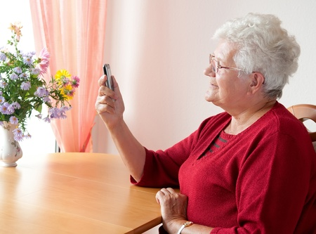 old woman reading a sms Stock Photo