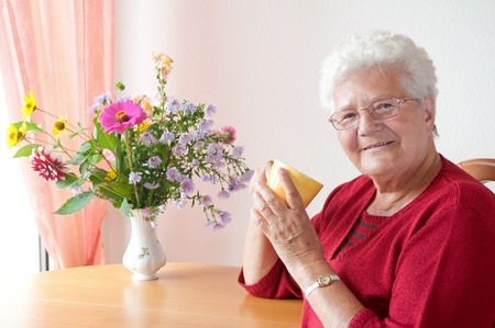 old gray-haired woman with cup photo