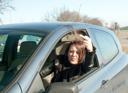 woman in the car shows the middle finger Stock Photo - 13327102