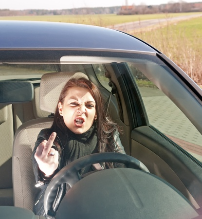 woman in the car shows the middle finger Stock Photo