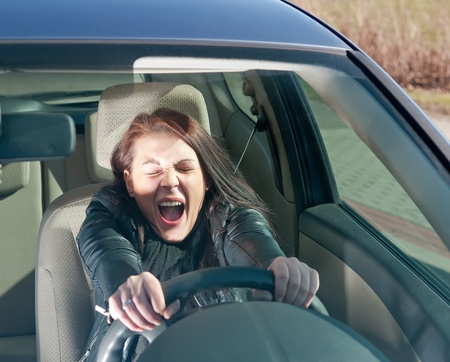 afraid young woman screaming in the car photo