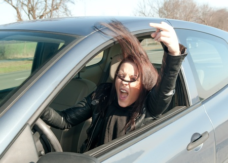 angry young woman in the car shows the middle finger photo