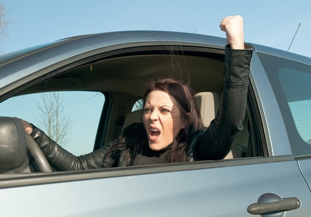 angry young woman in the car shows the fist photo