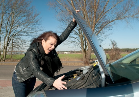 young woman has a car breakdown photo