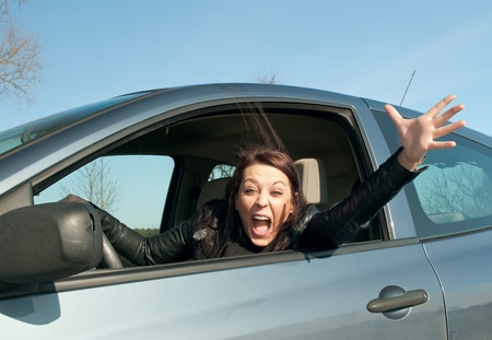 angry young woman screaming in the car  photo