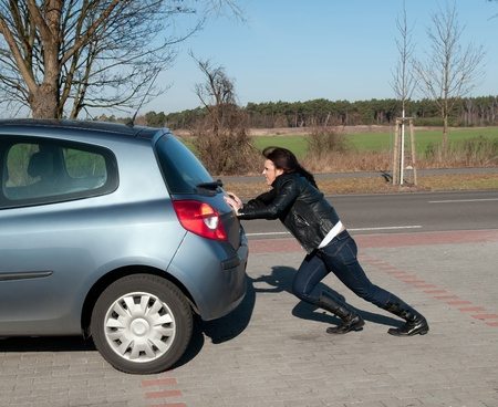pushing: geërgerd jonge vrouw duwt haar auto Stockfoto