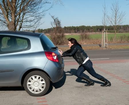 empujando: mujer joven molesto empuja su coche Foto de archivo