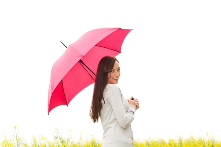 happy young woman with umbrella in canola field photo