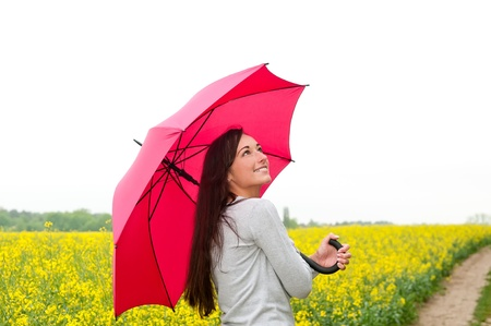 happy young woman with umbrella in canola field