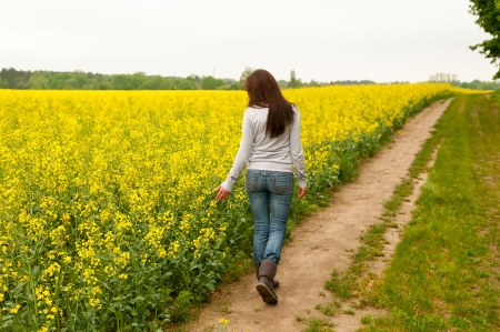 thoughtful young woman walking on rape field