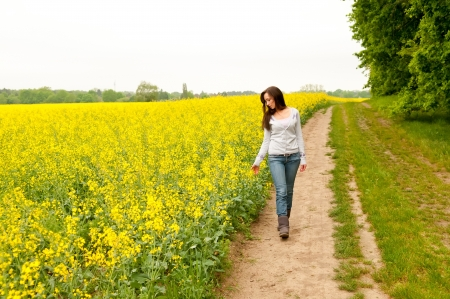 thoughtful young woman walking on rape field Stock Photo - 13859868