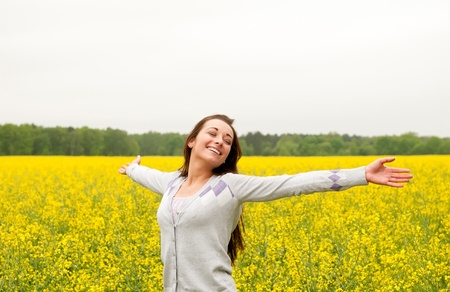 Young woman cheering in the rape field Stock Photo - 13859515