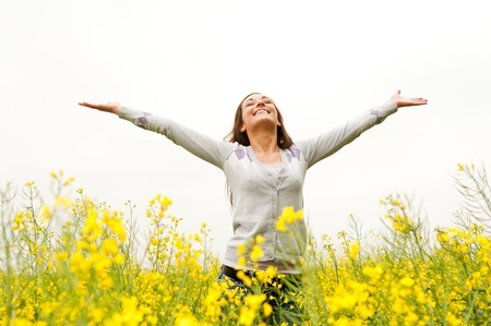 Young woman cheering in the rape field Stock Photo - 13859499