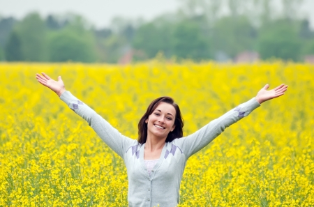 Young woman cheering in the rape field Stock Photo - 13859506