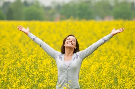 Young woman cheering in the rape field Stock Photo - 13859548
