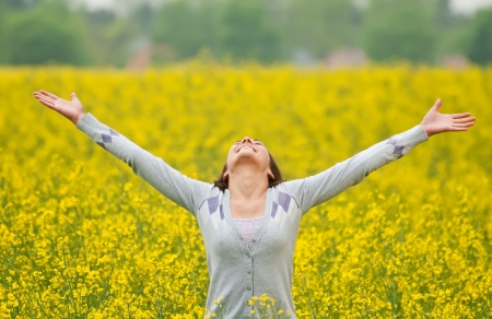 Young woman cheering in the rape field Stock Photo - 13859539