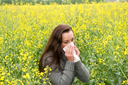 young woman in rape field  has hay fever photo