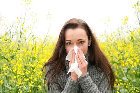 sneezing: giovane donna in campo di colza ha la febbre da fieno