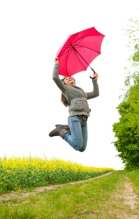 happy young woman jumping with umbrella photo