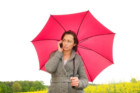 angry young woman with mobile phone under the umbrella photo
