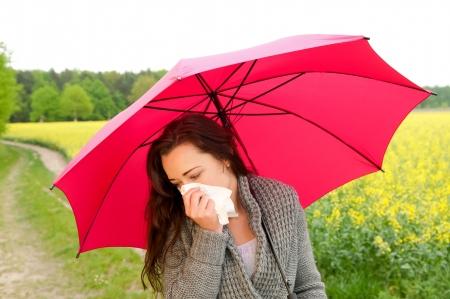 tosiendo: mujer joven con el paraguas rojo tiene la fiebre del heno