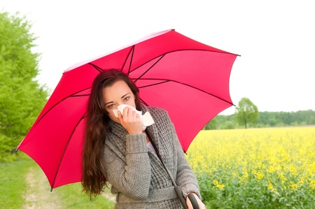 young woman with red umbrella  has hay fever