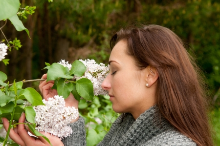 Young woman smelling the lilacs photo