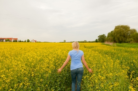 thoughtful young woman in rape field photo