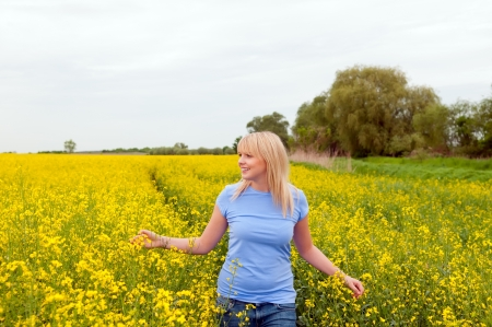 happy young woman in canola field photo