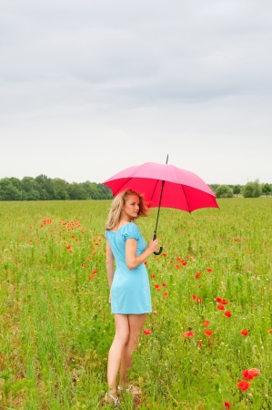 pretty young blond woman with red umbrella in a poppy field Stock Photo