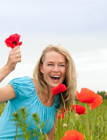 pretty young blond woman picking poppies photo
