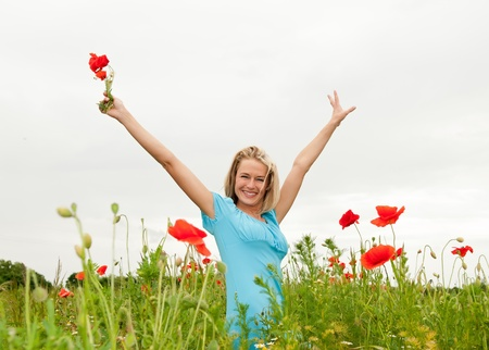 pretty young blond woman cheering in the poppy field Stock Photo - 14432623