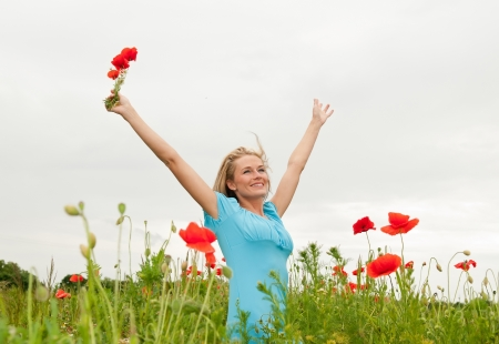 pretty young blond woman cheering in the poppy field Stock Photo - 14432622