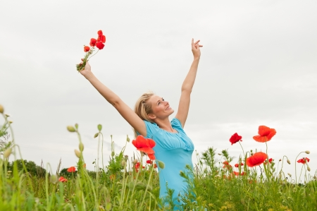 pretty young blond woman cheering in the poppy field photo