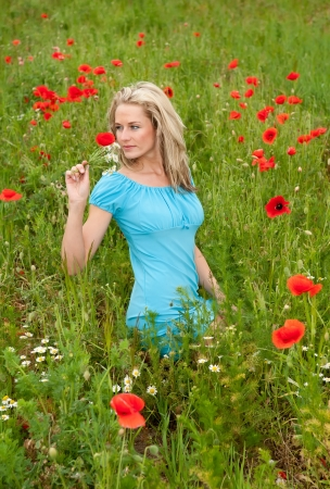 pretty young blond woman on a poppy meadow smelling a bouquet of flowers photo