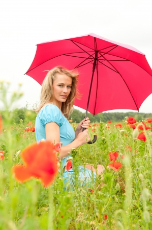 pretty young woman with red umbrella sitting in poppy field photo