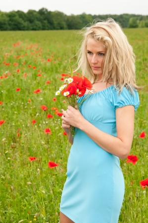 thoughtful young woman in poppy field photo