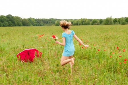 young beautiful blond woman walks through a poppy field, rear view photo