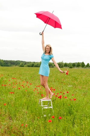 happy young blond woman with red umbrella in poppy field photo