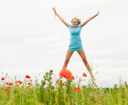 happy young blond woman jumping in a poppy field photo