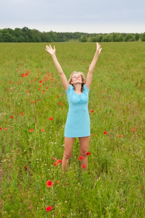 pretty young blond woman cheering in the poppy field Stock Photo - 14432670
