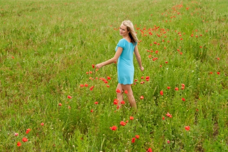 pretty young woman walking in poppy field photo