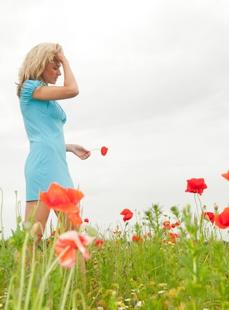 thoughtful young woman in poppy field