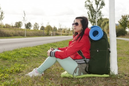 Hitchhiker sitting on the roadside Stock Photo - 15782071